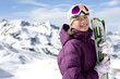 Portrait of smiling woman with skis on snowy mountain