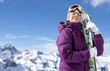 Woman with eyes closed holding skis on snowy mountain