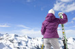Woman with skis looking at snowy mountains