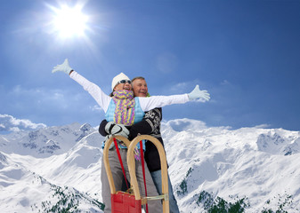 Man hugging woman with arms outstretched under sun on snowy mountain