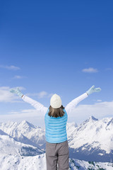 Woman standing with arms outstretched on snowy mountain top