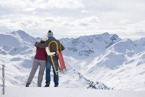 Senior couple with sled hugging on mountain top