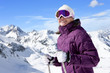 Smiling woman wearing ski goggles and holding ski poles on snowy mountain