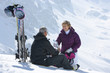 Senior couple with skis and water bottle sitting on snowy mountain