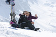 Smiling senior couple with skis taking self-portrait with digital camera on snowy mountain