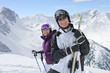 Portrait of smiling senior couple wearing sunglasses and holding skis on snowy mountain
