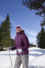 Smiling woman wearing ski goggles and holding ski poles in snow