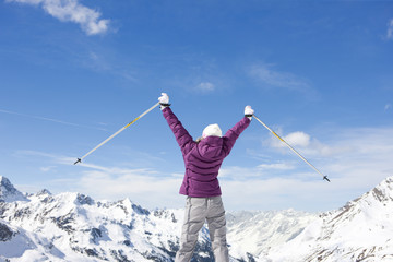 Woman holding ski poles with arms outstretched on snowy mountain top