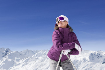 Smiling woman wearing ski goggles and leaning on ski poles on snowy mountain