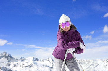 Portrait of smiling woman wearing ski goggles and leaning on ski poles on snowy mountain