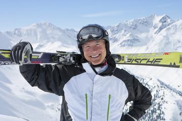 Portrait of smiling senior man with skis on snowy mountain top