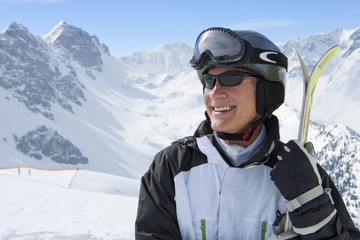 Smiling senior man wearing sunglasses and holding skis on snowy mountain