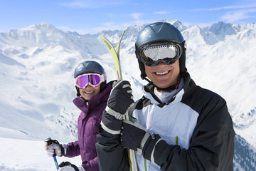 Portrait of smiling senior couple wearing ski goggles and holding skis on snowy mountain