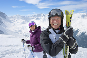 Portrait of smiling senior couple with skis on snowy mountain