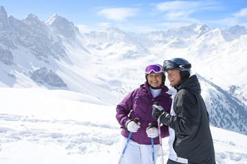 Smiling senior couple with ski poles on snowy mountain