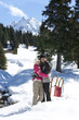 Portrait of smiling couple hugging in snow woods below mountain