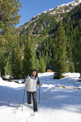 Portrait of smiling senior man with ski poles trekking in snow outside cabin