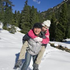 Portrait of couple piggybacking in snowy woods