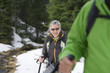 Portrait of smiling woman with ski poles trekking in snowy woods