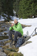 Smiling man with backpack and ski poles sitting at edge of stream in snowy woods