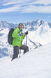 Portrait of smiling senior man with backpack and ski poles trekking on snowy mountain