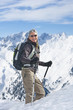 Portrait of smiling woman with backpack and ski poles trekking on snowy mountain