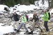 Senior couples with ski poles crossing stream in snowy woods