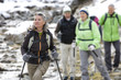 Senior couples with ski poles crossing stream