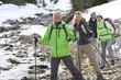 Portrait of smiling senior couples with ski poles crossing stream in snowy woods