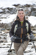 Portrait of smiling woman with ski poles crossing stream
