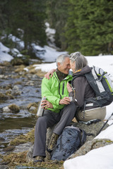 Couple with backpacks hugging at edge of stream in snowy woods