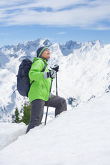 Senior man with backpack and ski poles trekking up slope on snowy mountain
