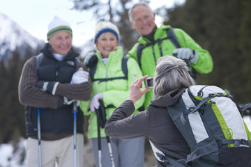 Woman taking photograph of senior friends in snowy woods