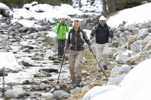 Smiling seniors with ski poles walking along stream