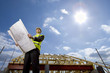 Sun in blue sky over architect holding blueprints at construction site