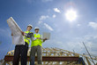 Sun in blue sky over architects holding blueprints and laptop at construction site