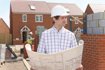 Architect holding blueprints at housing construction site