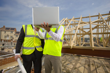 Architects with blueprints using laptop at construction site