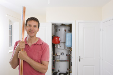 Portrait of smiling man with copper pipes in front of boiler in closet