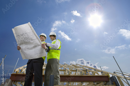 Sun in blue sky over architects holding blueprints at construction site