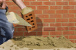Close up of bricklayer applying mortar to brick with trowel in front of wall