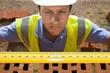 Close up of bricklayer holding carpenter rule along bricks on wall