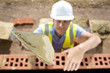 Bricklayer holding trowel over bricks on wall