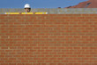 Bricklayer holding level tool on brick wall