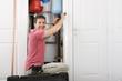 Portrait of smiling handyman fixing boiler in closet