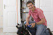 Portrait of smiling handyman with wrench kneeling before toolbox in front of boiler in closet