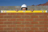 Portrait of bricklayer holding level tool on brick wall
