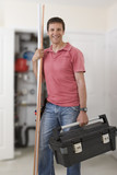 Portrait of smiling handyman holding toolbox and copper pipes in front of boiler in closet