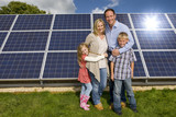Smiling family standing together near large solar panels