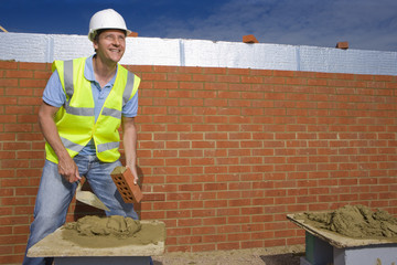Smiling bricklayer applying mortar to brick with trowel in front of wall
